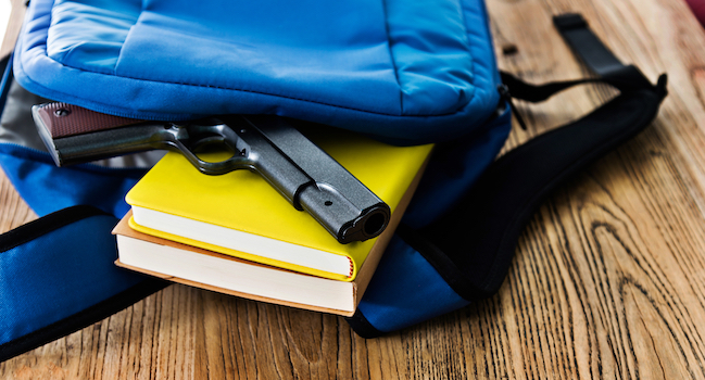 A handgun on top of books inside a backpack.
