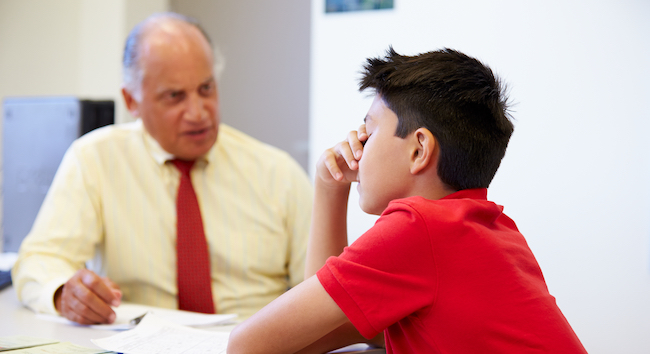 School counselor speaking to a student with hand over his face.