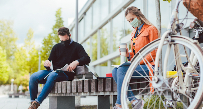 Students wearing face masks on a college campus.